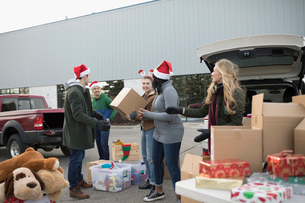 Young adult volunteers in Santa hats sorting Christmas donations in parking lotの写真素材 [FYI02326535]