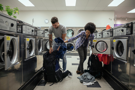 Young couple backpackers doing laundry at laundromatの写真素材 [FYI02326571]