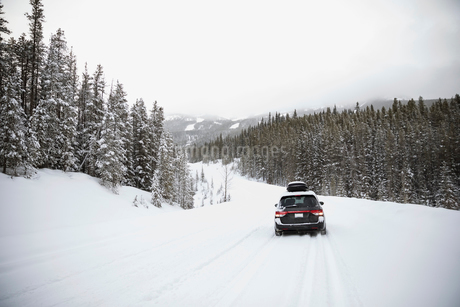 Car driving in remote snow covered landscapeの写真素材 [FYI02326633]