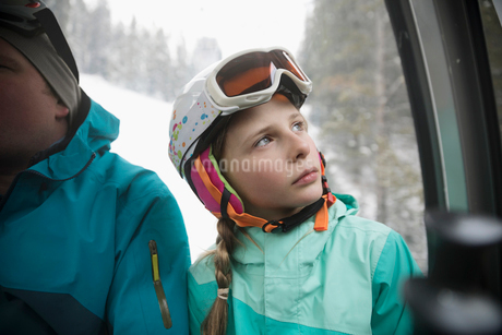 Curious, thoughtful girl skier riding gondola, looking at viewの写真素材 [FYI02326650]