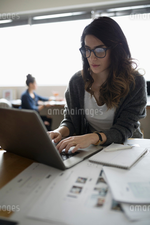Female photo editor working at laptop in officeの写真素材 [FYI02326651]