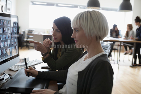 Female photo editors with graphics tablet editing digital photo proofs on computer in officeの写真素材 [FYI02326683]