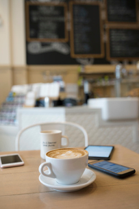 Still life cappuccino and smart phones on cafe tableの写真素材 [FYI02326684]