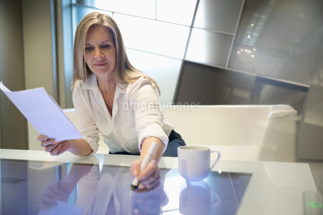 Businesswoman using interactive touch table in officeの写真素材 [FYI02326689]