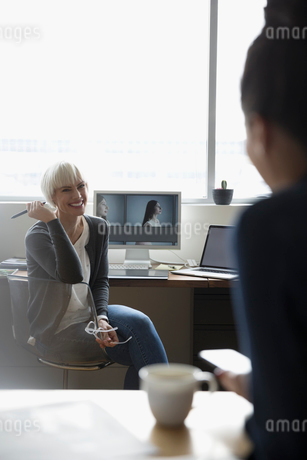 Female photo editor at computer talking to colleagueの写真素材 [FYI02326742]