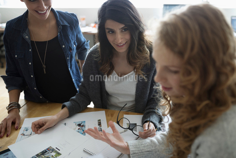 Female photo editors reviewing photo proofs in officeの写真素材 [FYI02326839]
