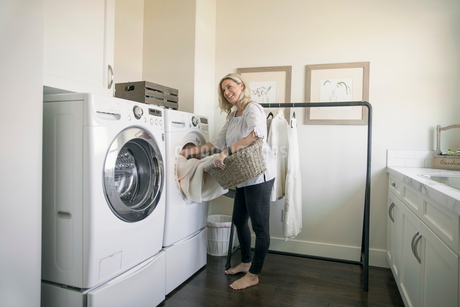 Woman removing laundry from dryer in laundry roomの写真素材 [FYI02326842]