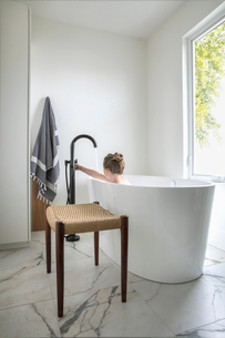 Girl taking a bath in soaking tub in bathroomの写真素材 [FYI02326854]