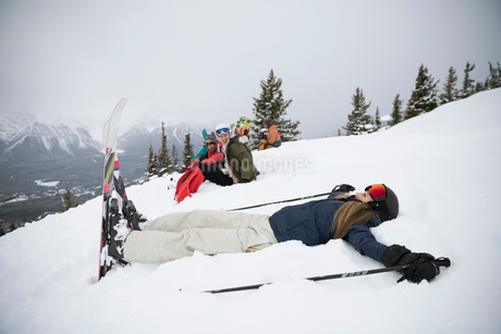 Playful female skier making snow angelsの写真素材 [FYI02326933]