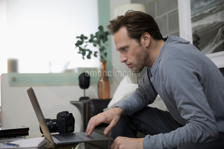 Male photographer with digital camera working at laptopの写真素材 [FYI02326948]
