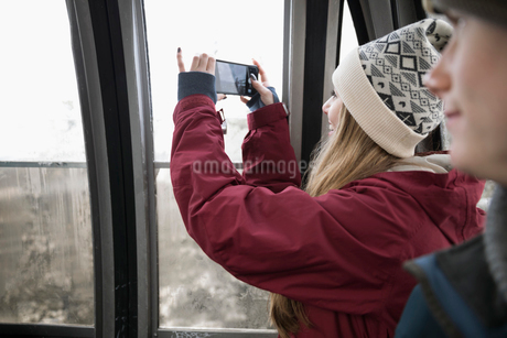 Teenage girl skier riding gondola, photographing viewing with camera phoneの写真素材 [FYI02326965]