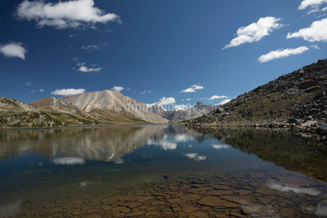 Reflection of clouds and craggy mountains on tranquil, placid lakeの写真素材 [FYI02326974]