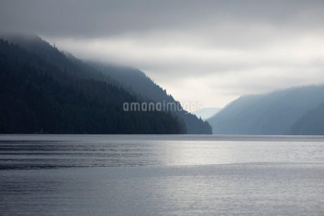 Tranquil silhouetted mountains and lake under cloudy skyの写真素材 [FYI02326991]