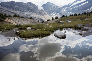 Reflection of clouds in tranquil, placid lake below mountainsの写真素材 [FYI02327034]