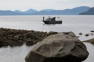 Fisherman fishing on fishing boat on remote lakeの写真素材 [FYI02327061]