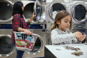 Girl counting coins, helping mother doing laundry at laundromatの写真素材 [FYI02327086]