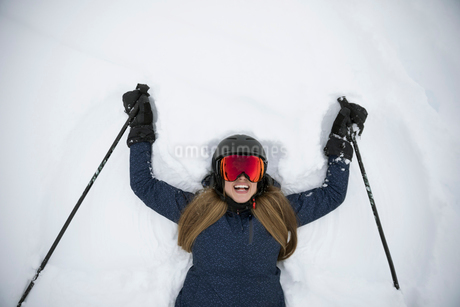 View from above portrait happy female skier making snow angelsの写真素材 [FYI02327145]