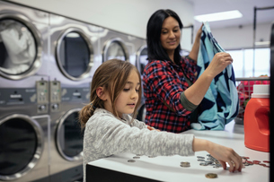 Daughter sorting coins, helping mother doing laundry at laundromatの写真素材 [FYI02327149]