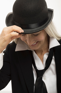 Confident, smiling senior woman wearing suit and hatの写真素材 [FYI02327182]