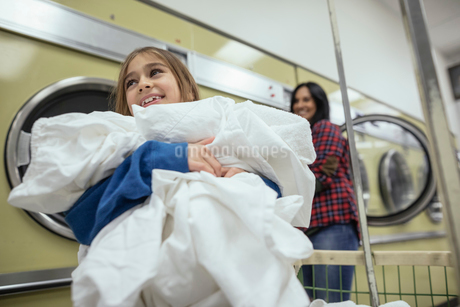Smiling mother and daughter doing laundry at laundromatの写真素材 [FYI02327236]