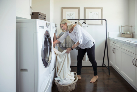 Woman removing laundry from dryer in laundry roomの写真素材 [FYI02327274]