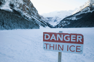 Danger Thin Ice sign on snowy mountain lakeの写真素材 [FYI02327326]