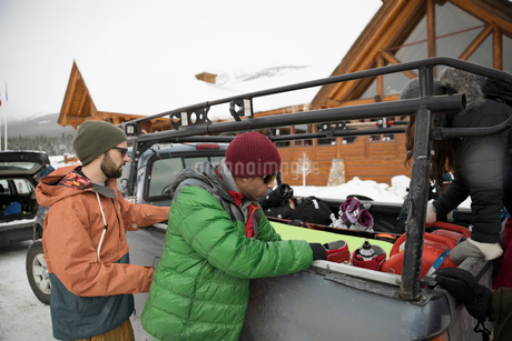 Male snowboarder friends unloading snowboarding equipment from truck at ski resortの写真素材 [FYI02327341]