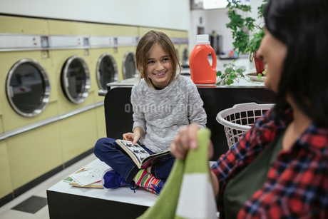 Daughter reading book, watching mother doing laundry at laundromatの写真素材 [FYI02327362]