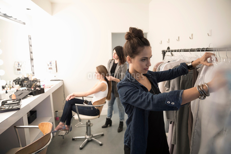 Female wardrobe stylist picking out clothes and hairstylist preparing model for photo shootの写真素材 [FYI02327395]