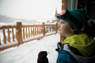 Curious boy skier anticipating, looking out window at ski resort lodgeの写真素材 [FYI02327405]