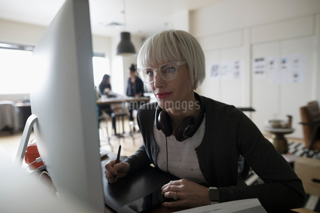 Focused female graphic designer using graphics tablet, leaning toward computer in officeの写真素材 [FYI02327449]
