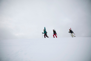 Female skier and snowboarder friends hiking along snow covered ridgeの写真素材 [FYI02327463]