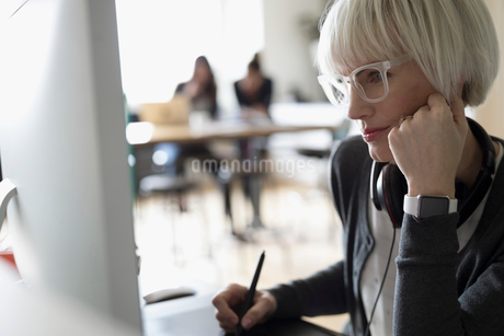 Focused female graphic designer using graphics tablet at computerの写真素材 [FYI02327522]