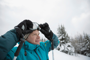 Male skier adjusting goggles in snowの写真素材 [FYI02327585]