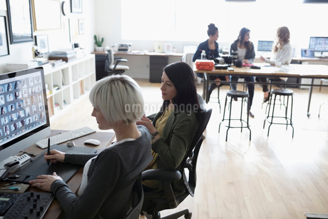 Female photo editors with graphics tablet editing digital photo proofs on computer in officeの写真素材 [FYI02327586]