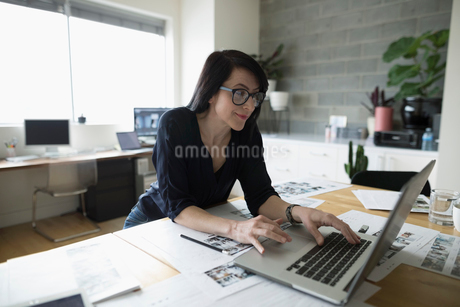 Female photo editor working at laptop, reviewing photo proofs in officeの写真素材 [FYI02327622]