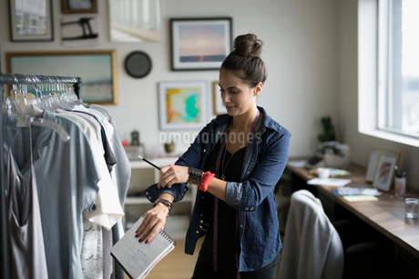 Female wardrobe stylist rolling up sleeves at clothing rack in officeの写真素材 [FYI02327647]