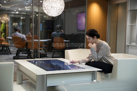 Focused businesswoman using interactive touch table in officeの写真素材 [FYI02327662]