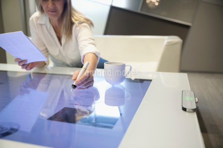 Businesswoman using interactive touch table in officeの写真素材 [FYI02327716]