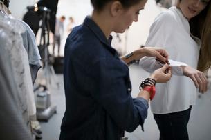 Female wardrobe stylist adjusting blouse sleeve for model at photo shoot in studioの写真素材 [FYI02327728]