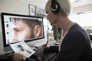 Female photo editor with headphones using graphics tablet, editing digital photograph on computerの写真素材 [FYI02327759]