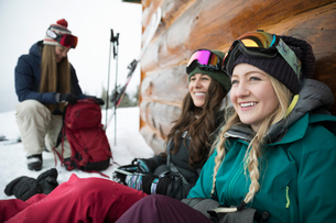Smiling female skier friends resting along cabinの写真素材 [FYI02327785]
