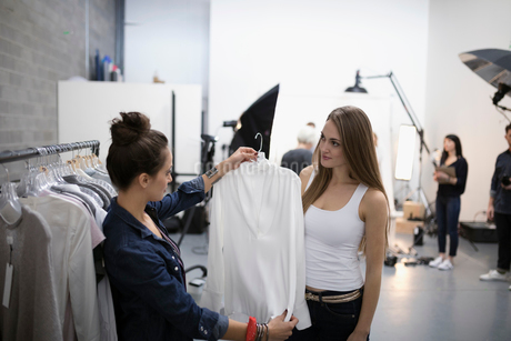 Female wardrobe stylist choosing blouse for model at photo shoot in studioの写真素材 [FYI02327823]