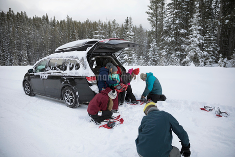 Family preparing for snowshoeing at car in remote snowの写真素材 [FYI02327954]