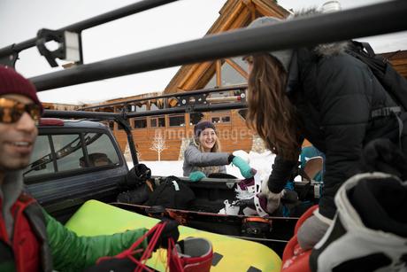 Friends unloading snowboarding equipment from truck at ski resortの写真素材 [FYI02327962]