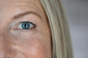 Close up confident mature woman with blue eyes and smile linesの写真素材 [FYI02327982]