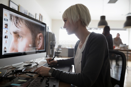 Female photo editor using graphics tablet, editing digital photograph on computer in officeの写真素材 [FYI02327984]