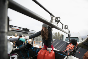 Friends unloading snowboarding equipment from truck at ski resortの写真素材 [FYI02328080]