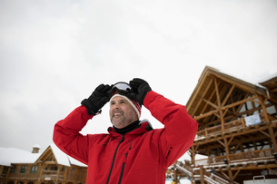 Smiling male skier adjusting goggles outside ski resort lodgeの写真素材 [FYI02328193]