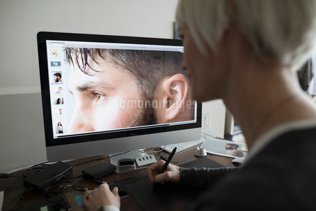 Female photo editor using graphics tablet, editing digital photograph on computer in officeの写真素材 [FYI02328223]